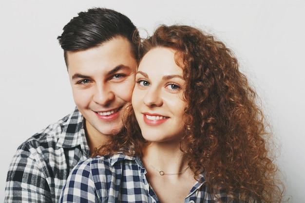 Bliska uroczej pary rodzinnej przytula się i patrzy radośnie na aparat