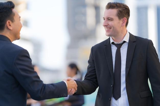 Bliska, uścisk dłoni dwóch biznesmenów na tle nowoczesnego biura, koncepcja partnerstwa, uścisk dłoni, aby przypieczętować umowę