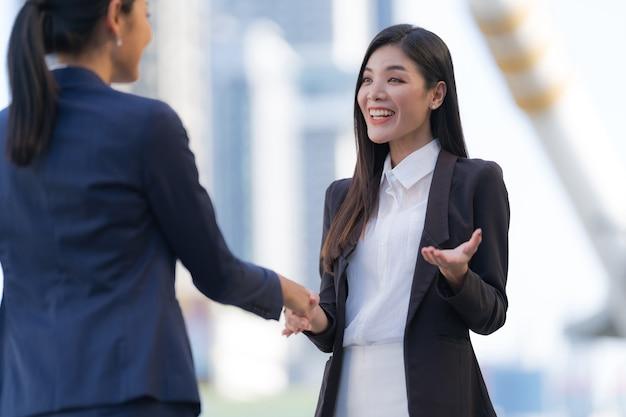 Bliska, uścisk dłoni dwóch kobiet biznesu na tle nowoczesnego biura, koncepcja partnerstwa, uścisk dłoni, aby przypieczętować umowę