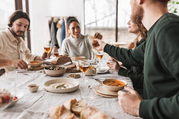 Bliska uśmiechnięta african american kobieta siedzi przy stole, szczęśliwie biorąc kromkę chleba od przyjaciela