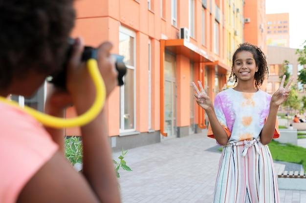 Bliska uśmiechnięta dziewczyna pozuje na zewnątrz