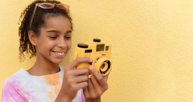 Bliska uśmiechnięta dziewczyna trzyma aparat