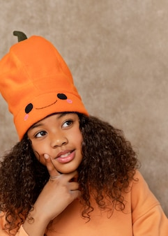 Bliska uśmiechnięta dziewczyna z dyniowym kapeluszem
