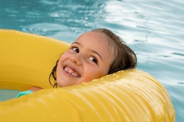 Bliska uśmiechnięta dziewczyna z kołem ratunkowym