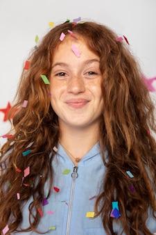 Bliska uśmiechnięta dziewczyna z konfetti