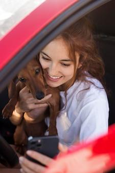 Bliska uśmiechnięta kobieta biorąca selfie z psem
