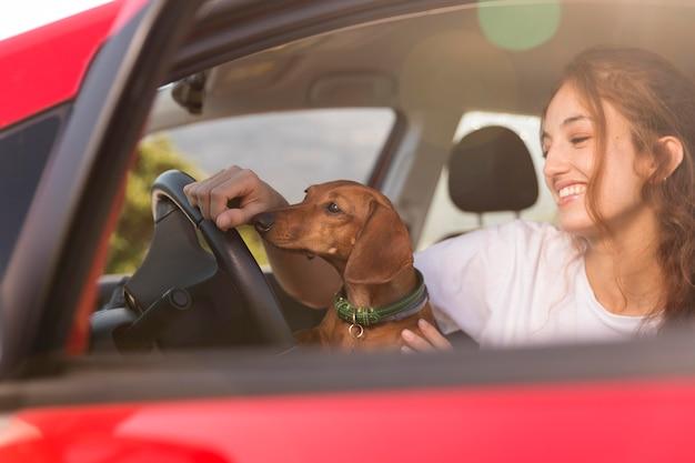 Bliska uśmiechnięta kobieta jadąca z psem