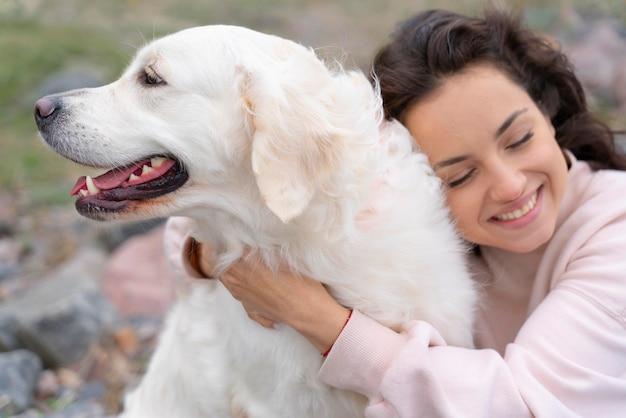 Bliska uśmiechnięta kobieta przytulająca psa