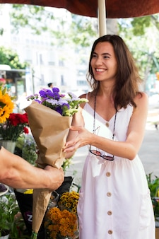 Bliska uśmiechnięta kobieta trzyma kwiaty