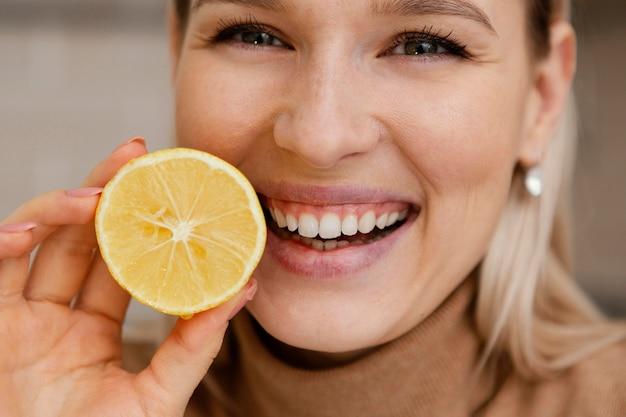 Bliska uśmiechnięta kobieta trzyma plasterek cytryny