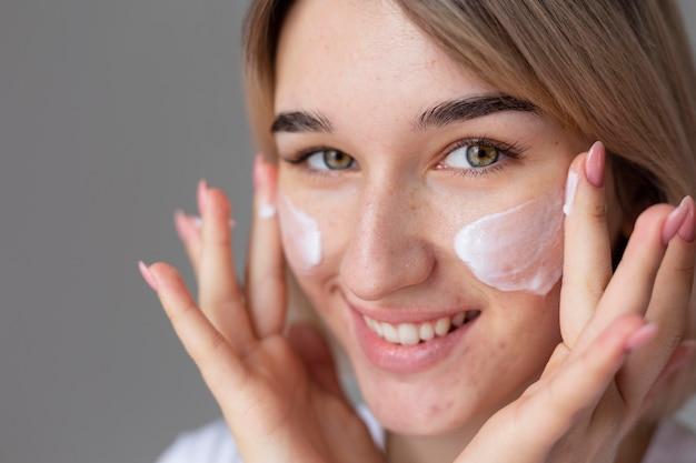 Bliska uśmiechnięta kobieta używa kremu do twarzy