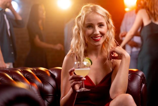 Bliska uśmiechnięta kobieta w barze z drinkiem