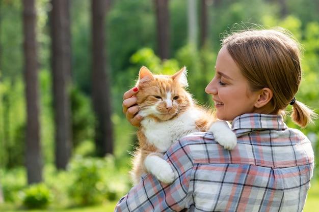Bliska uśmiechnięta kobieta w kraciastej koszuli, przytulanie i obejmowanie z czułością i miłością domowego imbirowego kota, głaszcząc po głowie, na zewnątrz w słoneczny dzień.