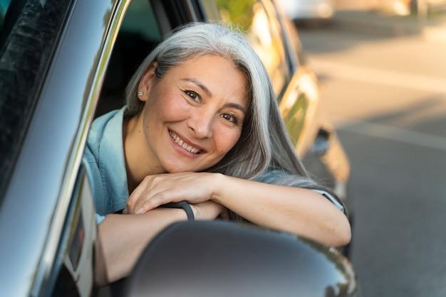 Bliska uśmiechnięta kobieta w samochodzie