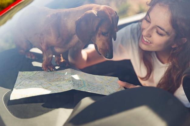 Bliska uśmiechnięta kobieta z psem i mapą