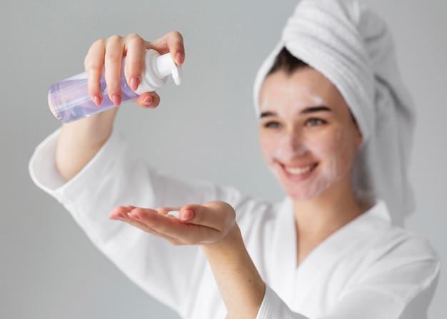 Bliska uśmiechnięta kobieta za pomocą produktu do twarzy