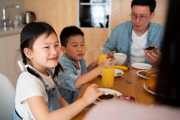 Bliska uśmiechnięta rodzina jedząca razem