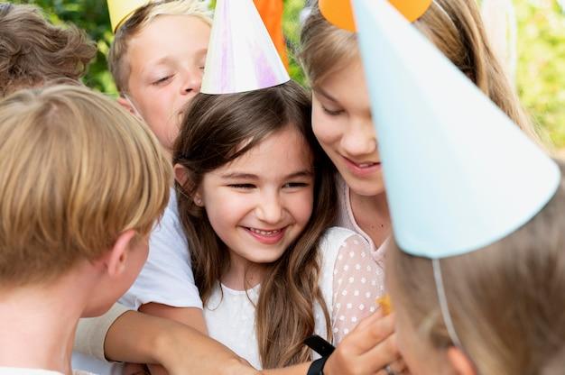 Bliska uśmiechnięte dzieci w czapkach imprezowych