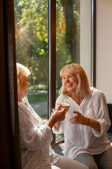 Bliska uśmiechnięte kobiety trzymające kubki