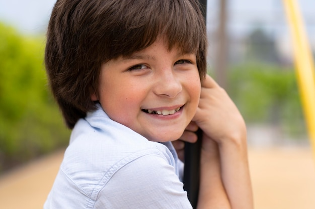 Bliska uśmiechniętego chłopca na huśtawce