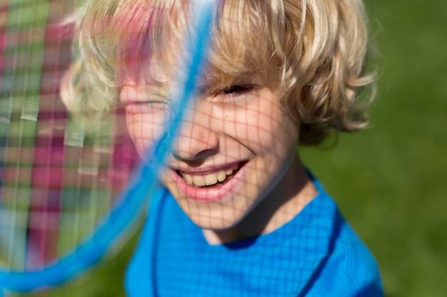 Bliska uśmiechniętego chłopca z rakietą do badmintona