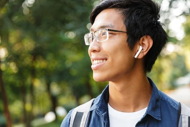 Bliska uśmiechnięty azjatycki student płci męskiej w okularach i słuchawkach słuchanie muzyki, patrząc od hotelu