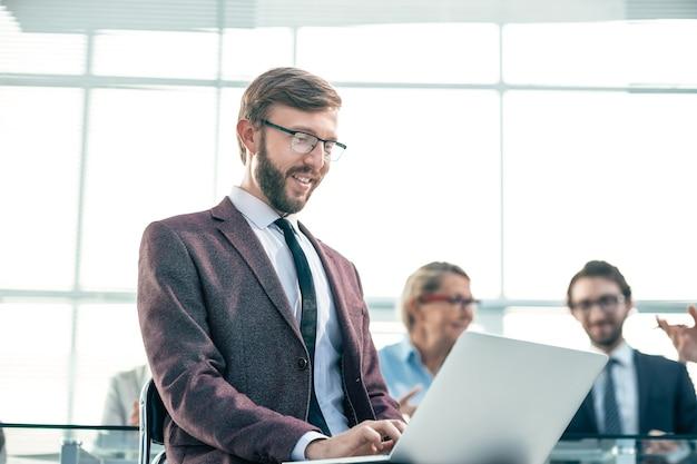 Bliska uśmiechnięty biznesmen pracuje na laptopie ludzie i technologia