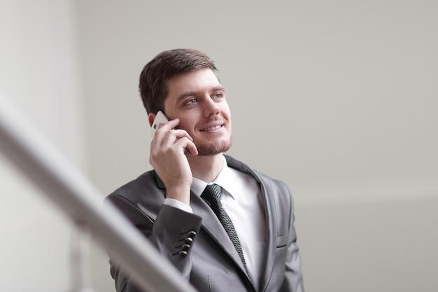 Bliska uśmiechnięty biznesmen rozmawia na smartfonie w biurze