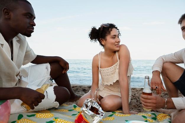 Bliska uśmiechniętych przyjaciół siedzących na plaży