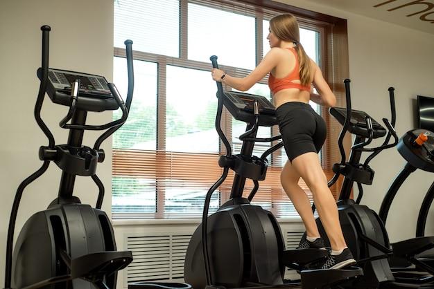 Bliska widok kobiety z tyłu na eliptyczny trener w siłowni