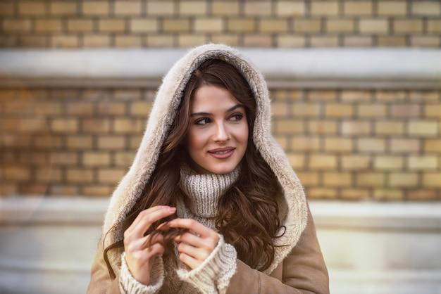 Bliska widok ostrości portret z kapturem zadowolony, wesoły, stylowy, atrakcyjny, piękna, młoda, szczęśliwa dziewczyna w swetrze i kurtce, patrząc daleko, bawiąc się włosami na ulicy miasta.