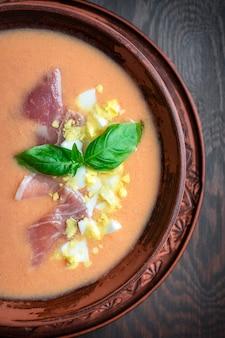 Bliska widok salmorejo orzeźwiająca hiszpańska zupa z blendowanych pomidorów spożywana z jamonem i bazylią