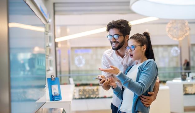 Bliska widok z boku ślicznej podekscytowanej uroczej młodej dziewczyny studentki, wskazując rękami na dużym nowym telewizorze, podczas gdy jej brodaty przystojny uśmiechnięty chłopak przytula ją w sklepie technicznym.