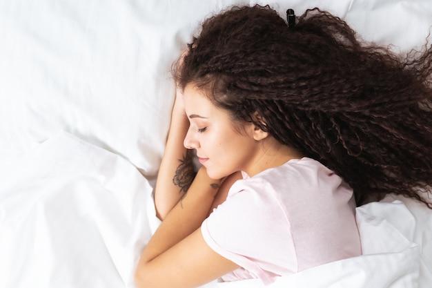 Bliska widok z góry pięknej kobiety afro włosów śpiącej na śnieżnobiałej prześcieradle leżącej na dużym łóżku. copyspace.