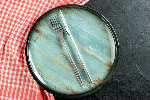 Bliska widok z góry stalowy widelec i nóż obiadowy na okrągłym talerzu czerwony i biały obrus w kratkę na czarnym stole