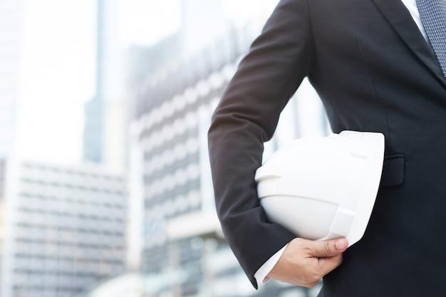 Bliska widok z przodu inżynierii biznes człowiek garnitur wykonawcy pracownik budowlany trzyma biały kask bezpieczeństwa dla bezpieczeństwa operacji pracy.