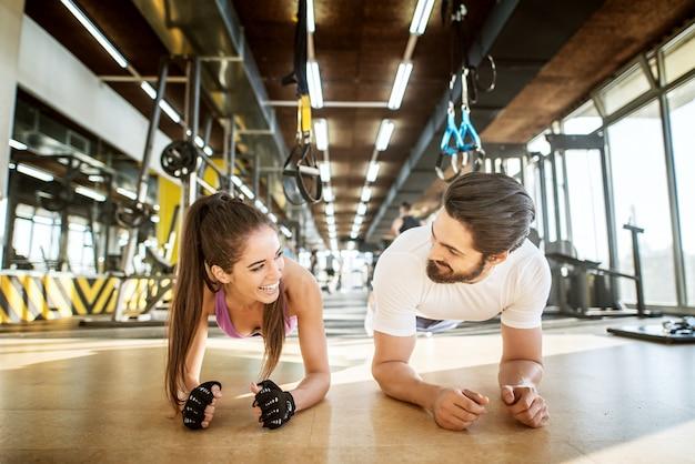 Bliska widok z przodu uroczej uśmiechniętej atrakcyjnej dziewczyny robi deski, stojąc ze swoim osobistym trenerem w słonecznej siłowni, patrząc na siebie.