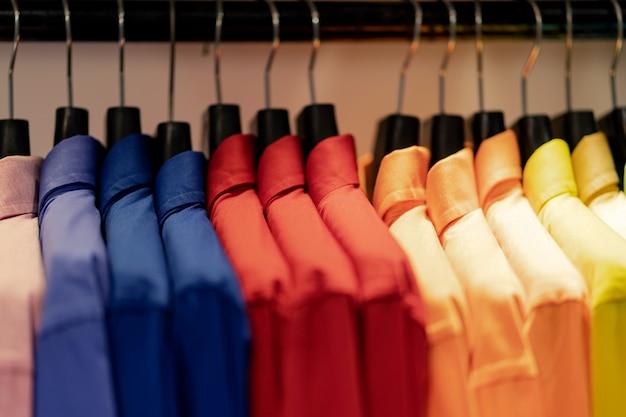Bliska wielu kolorowych koszul na wieszakach, kolorowe ubrania tkaniny