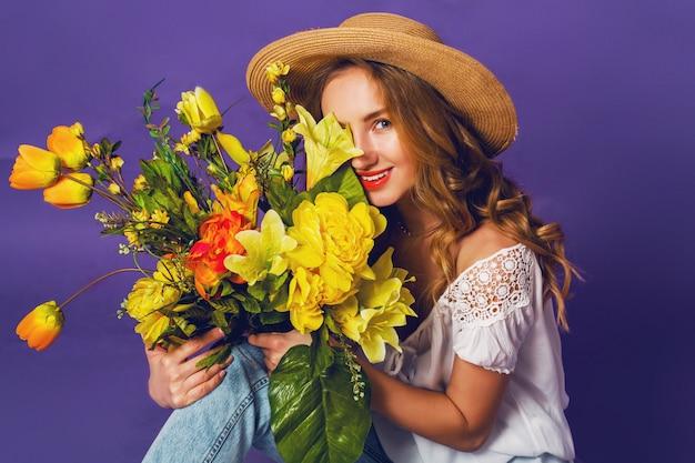 Bliska wiosna portret pięknej blondynki młodej damy w stylowym słomkowym kapeluszu letnim, trzymając kolorowy wiosenny bukiet kwiatów w pobliżu fioletowego tła ściany.