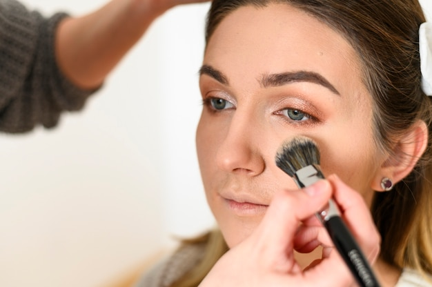 Bliska wizażystka pracuje nad makijażem ślubnym
