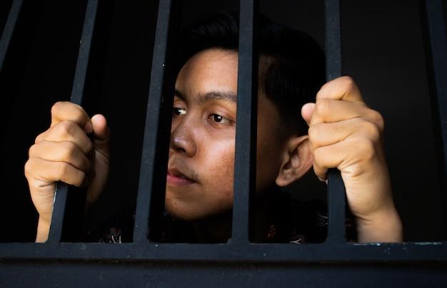 Bliska wyraz człowieka posiadającego kraty w więzieniu. wygląda smutno i przepraszam. pojęcie korupcji