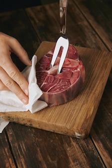 Bliska wytatuowany rzeźnik ręka trzyma widelec do mięsa w świeżym surowym steku na obiad, nie do poznania
