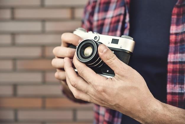 Bliska zdjęcie człowieka z retro aparatu fotograficznego moda podróże styl życia na zewnątrz