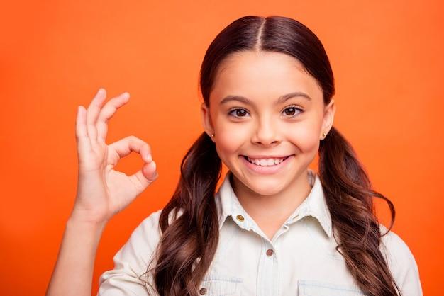 Bliska zdjęcie pozytywnej pewnej siebie małej dziewczynki chce polecić świetne reklamy promocyjne pokazują w porządku znak nosić strój w stylu casual izolowane pomarańczowe tło