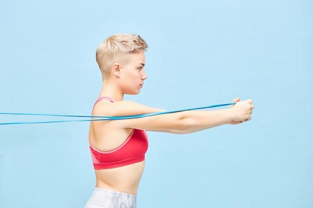 Bliska zdjęcie profilowe zdeterminowanej, młodej, krótkowłosej kobiety w strojach sportowych, używającej oporu do wzmocnienia górnej części ciała. koncepcja zdrowego, aktywnego stylu życia, energii i motywacji