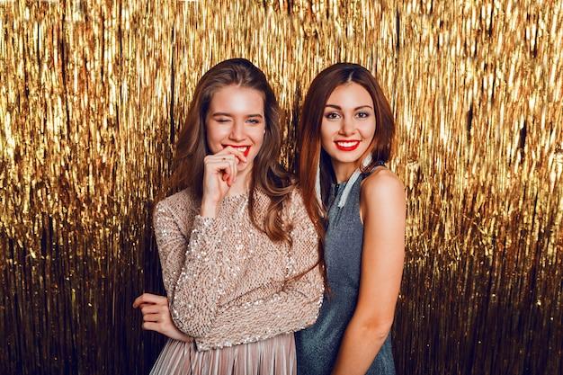 Bliska zdjęcie studyjne dwóch niesamowitych seksownych celebrujących dziewczyn z czerwonymi ustami i niespodzianką