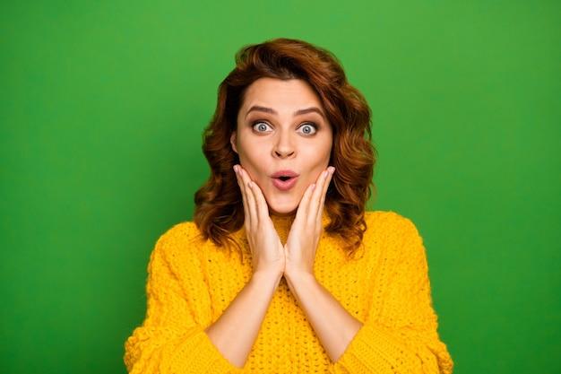 Bliska zdjęcie zdumionej kobiety wygląda dobrze niesamowita jesień nowość pod wrażeniem dotyk dłonie policzki krzyk krzyk nosić sweter izolowany na jasnej ścianie koloru