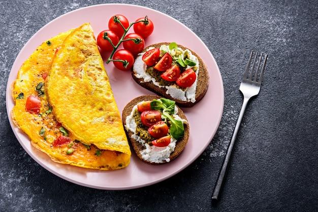 Bliska, zdrowe śniadanie omlet jajeczny, pełnoziarniste tosty z twarogiem, pesto i pomidorami cherry na różowym talerzu, na czarnym tle kamienia z miejsca na kopię.