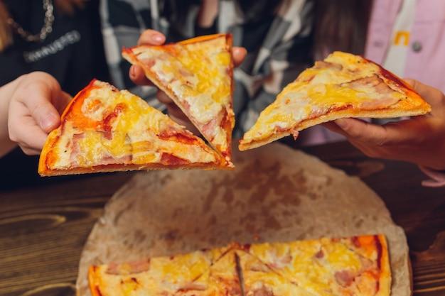 Bliska żeńska ręka trzyma, biorąc kawałek, kawałek pizzy przyjaciele siedzieli razem w kawiarni
