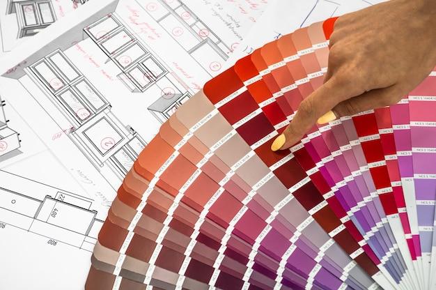 Bliska żeńska ręka trzyma wielobarwne próbki do malowania wnętrz lub mebli na tle nowej budowy lub remontu domu